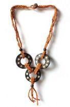 Ce collier est constitué d\'une multitude de perle orange, avec en son centre trois beaux pendentif en bois de sono.